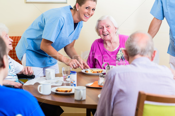 Group of seniors having food in nursing home Stock photo © Kzenon