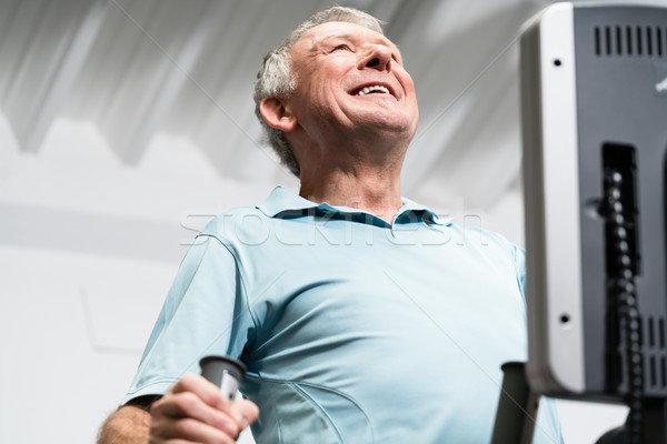 Elderly man training on cross trainer at the gym Stock photo © Kzenon