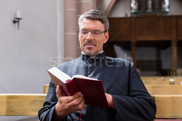 Priest sitting in church reading the bible Stock photo © Kzenon