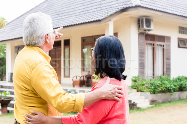Elderly man pointing to a comfortable residential house while st Stock photo © Kzenon
