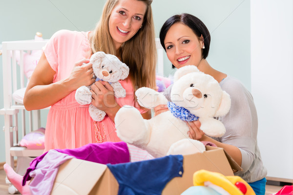 Heavily pregnant woman and friend arranging childs room  Stock photo © Kzenon