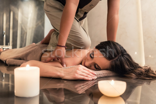 Young woman enjoying the acupressure techniques of Thai massage Stock photo © Kzenon