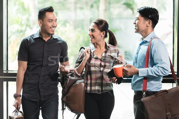Három fiatal derűs alkalmazottak munkahely beszél Stock fotó © Kzenon