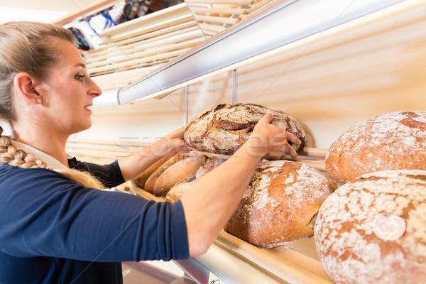 Bakery woman putting bread in shop shelf Stock photo © Kzenon