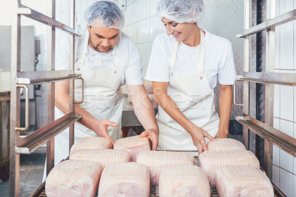 Butcher man and woman preparing meat for further processing Stock photo © Kzenon