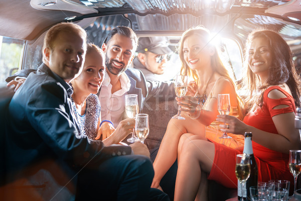 Group of party people in a limo drinking Stock photo © Kzenon