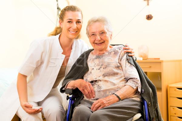 Young nurse and female senior in nursing home Stock photo © Kzenon