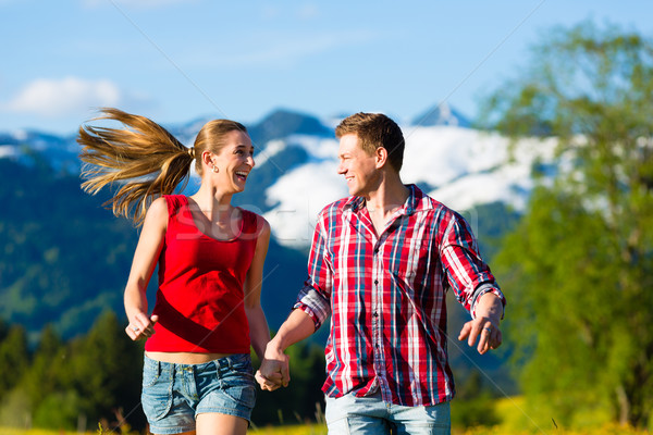 Stock photo: Couple running in the meadow with mountain
