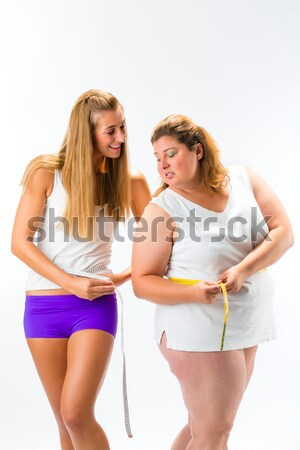 Thin and fat woman measuring waist with tape Stock photo © Kzenon