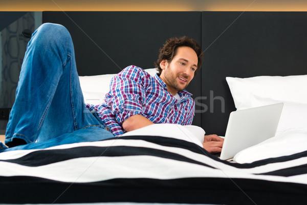 Jonge man hotel bed wifi computer hotelkamer Stockfoto © Kzenon