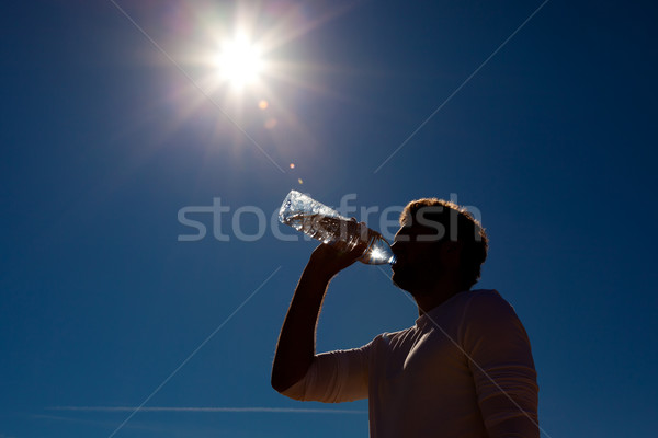 Człowiek pitnej woda butelkowana słońce woda pitna butelki Zdjęcia stock © Kzenon