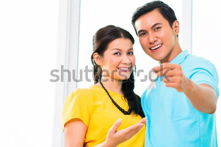 Young Asian couple in apartment with thumbs up Stock photo © Kzenon