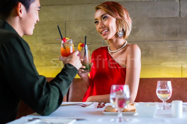 Asian couple drinking cocktails in fancy bar Stock photo © Kzenon