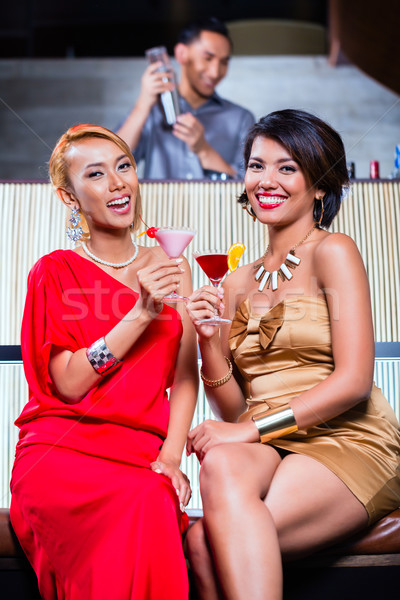 Asian women drinking cocktails in fancy bar Stock photo © Kzenon