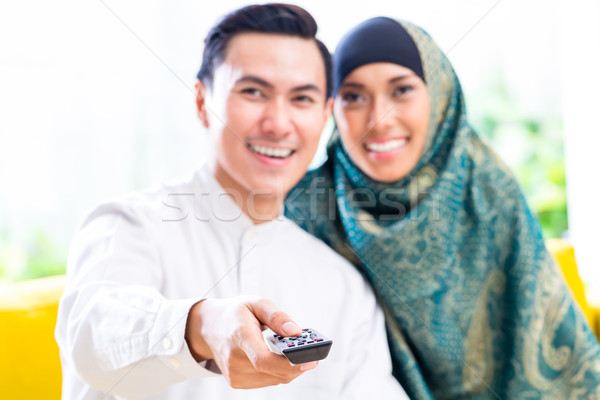 Asian Muslim Couple switching TV with remote control Stock photo © Kzenon
