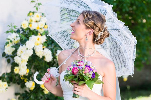 Bride at wedding with parasol in garden Stock photo © Kzenon