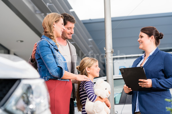 Car dealer advising family on buying auto Stock photo © Kzenon