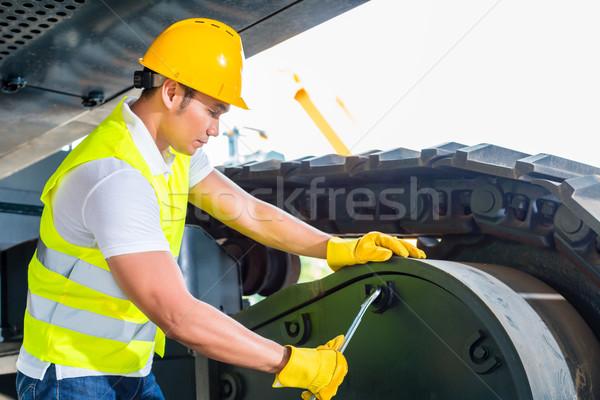 Asian mechanic repairing construction vehicle Stock photo © Kzenon