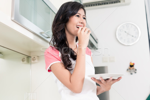Indonesian woman eating cookies in her kitchen Stock photo © Kzenon