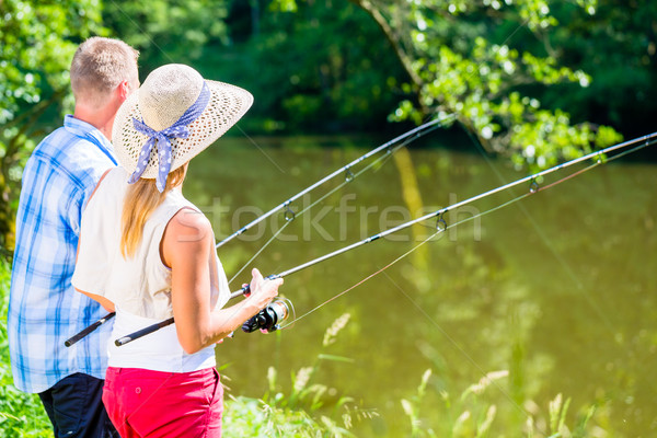Fishing man and woman together with rod at the river side Stock photo © Kzenon