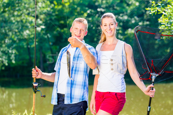 Fishing couple, man and woman, on lake being proud of catch Stock photo © Kzenon