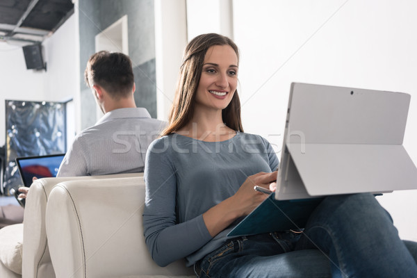 Woman sitting in armchair with smartphone and laptop PC Stock photo © Kzenon