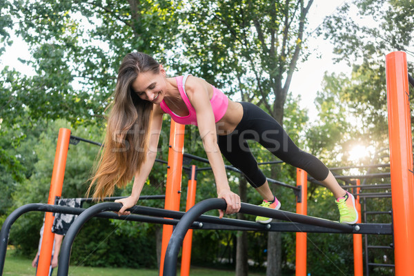 Cheerful beautiful woman exercising basic plank position outdoor Stock photo © Kzenon