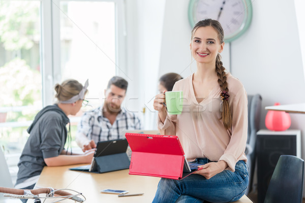 Portrait of a confident young woman sitting on the desk of a co- Stock photo © Kzenon