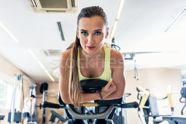 Low-angle view portrait of a cheerful woman during cycling workout Stock photo © Kzenon