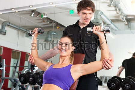 Handsome personal trainer guiding a beautiful woman at a modern fitness Stock photo © Kzenon