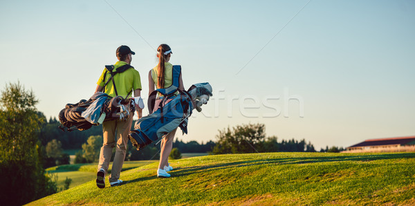 Stock photo: Happy couple wearing golf outfits while carrying stand bags