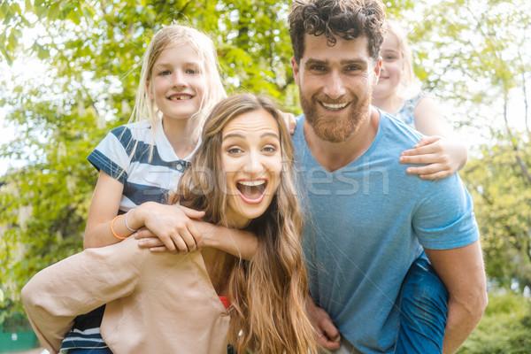 Család négy szórakozás hordoz gyerekek háton Stock fotó © Kzenon