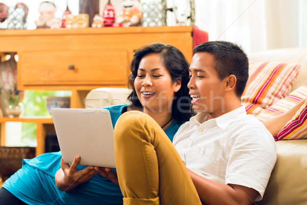Asian people sitting in front of a notebook laughing  Stock photo © Kzenon