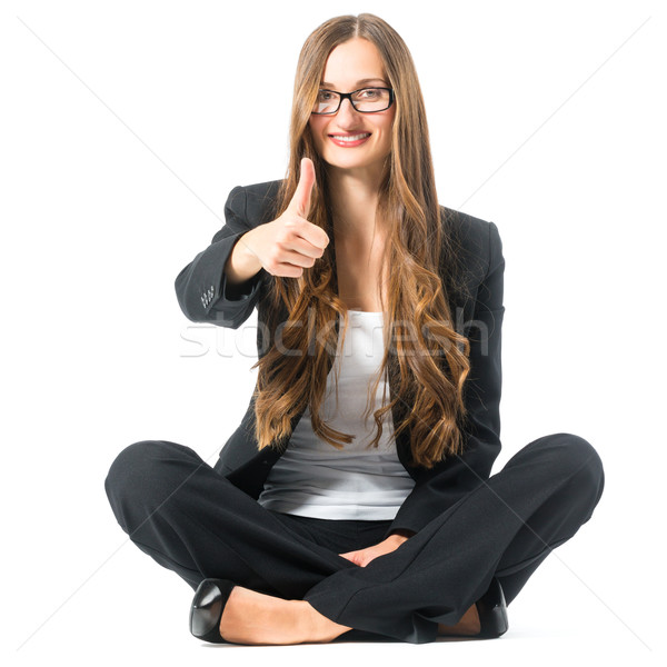 Young woman showing success sitting cross legged Stock photo © Kzenon