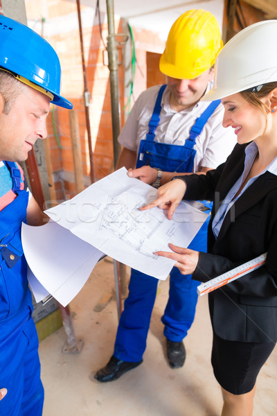 Work Team on construction site controlling floor plan Stock photo © Kzenon
