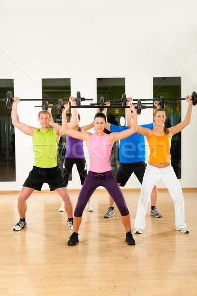 Fitness group with barbell in gym Stock photo © Kzenon