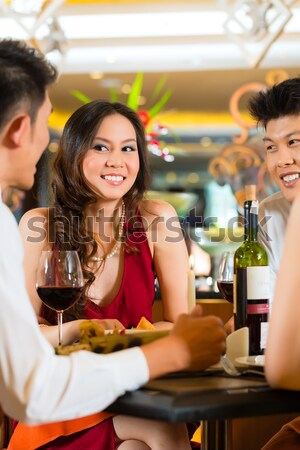 Waiter serving Chinese woman red wine in fancy restaurant Stock photo © Kzenon