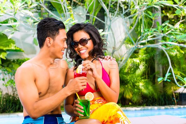 Asian couple drinking  cocktails at pool Stock photo © Kzenon