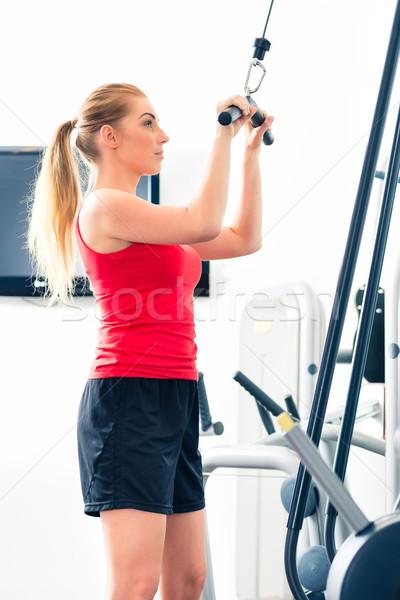 Woman training in gym or sport center Stock photo © Kzenon