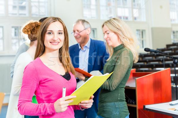 Students asking professor in college auditorium Stock photo © Kzenon