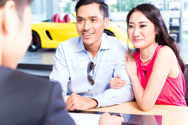 Asian Couple signing sales contract for car at dealership Stock photo © Kzenon