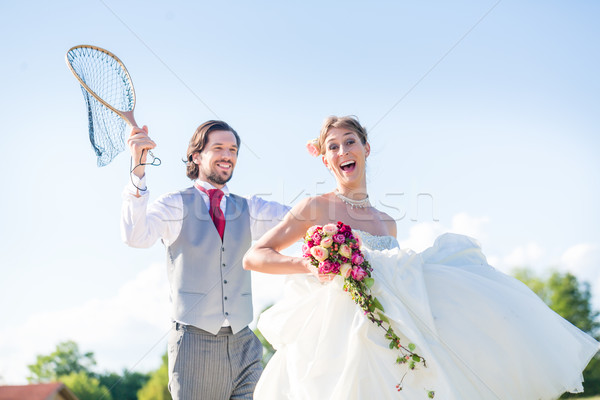 Wedding groom catching bride with net Stock photo © Kzenon