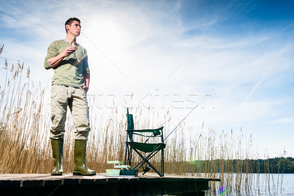 Angler standing on jetty having food for breakfast Stock photo © Kzenon