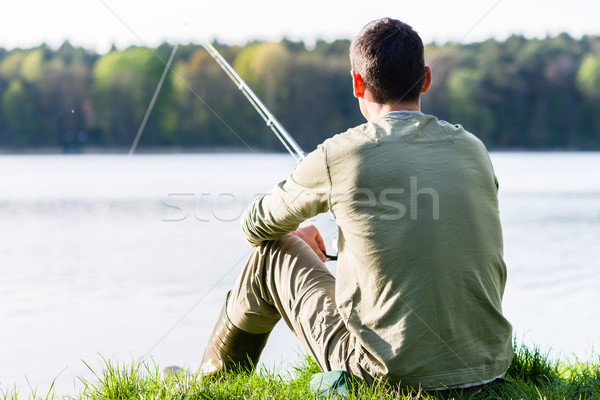 Angler sitting in grass at lake fishing with his rod Stock photo © Kzenon