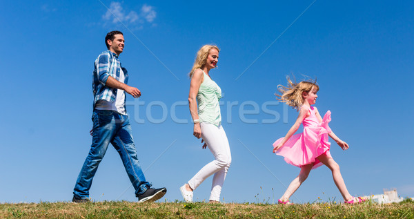 Family walks on meadow, Daughter leads, parents follow Stock photo © Kzenon