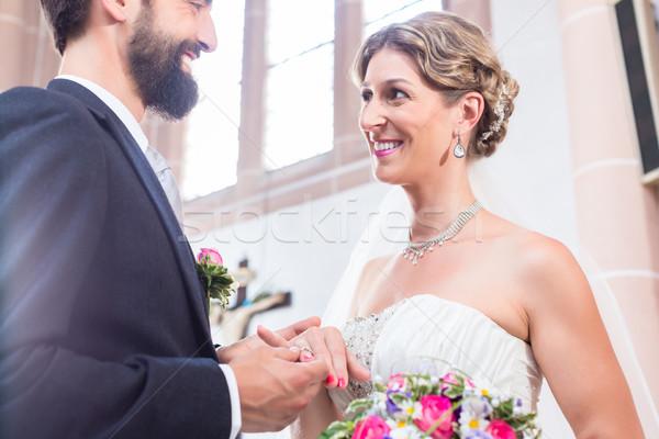 Groom slipping ring on finger of bride at wedding Stock photo © Kzenon