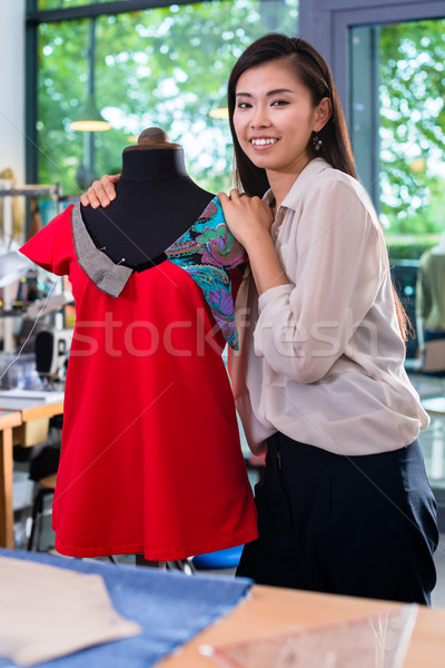 Asian tailor adjusts garment design on mannequin Stock photo © Kzenon