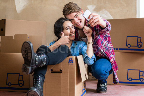 Happy young man and woman making a selfie after moving in into a Stock photo © Kzenon