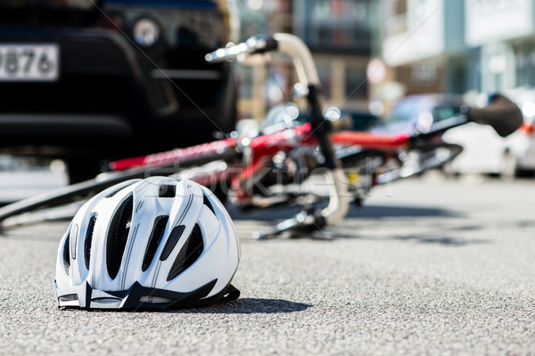 Stock photo: Close-up of a bicycling helmet on the asphalt  next to a bicycle