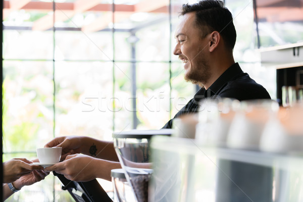 Friendly bartender serving a short espresso to a customer Stock photo © Kzenon